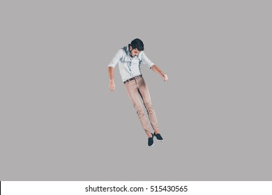 Free Falling Mid Air Shot Of Handsome Young Man Jumping And Gesturing Against Background
