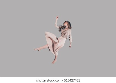 Free falling. Studio shot of attractive young woman hovering in air