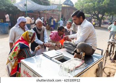 Free feeding in the streets of India. Believers distribute food and water near the temple during parikramy pilgrims.India, Govardhan, November 2017