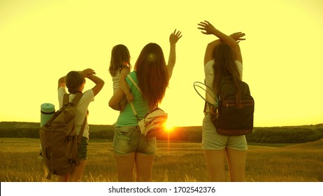 free girls travel with backpacks wave their hands and enjoy the sunset. Healthy Mom and kids tourists. girls travel in sunset light. Hiker Girl. mother with daughters travelers