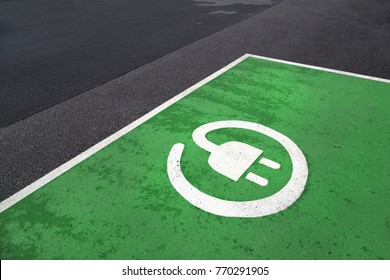 Free green colored electric vehicle parking station painted on asphalt floor.