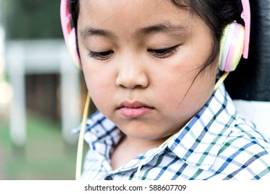 free happy cute girl enjoying. A beautiful kids hipster girl listening to music on headphones in the park.