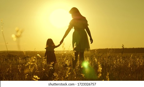 free Happy family with child walks in countryside. healthy Mother and baby are resting in park. happy childhood. little daughter and mother walk across field holding hands. baby holds mom's hand.