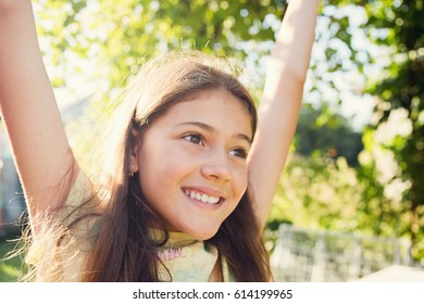 Free happy little girl enjoying nature, sunshine with raising hands. Freedom, happiness and enjoyment concept.