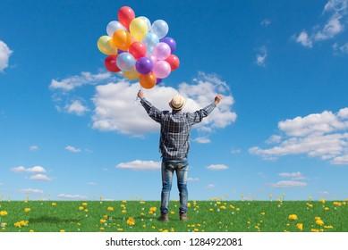 free happy man enjoying sunrise. man with holding balloon in blue sky enjoying peace