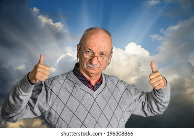 Free happy retired senior man with glasses enjoying the outdoors with cloudy sky and shows thumb up.