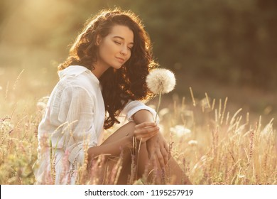 Free Happy Woman Enjoying Nature. Beauty Girl Outdoor. Freedom concept. Beauty Girl with dandelion, sunny flowers field. Sunbeams. Enjoyment and tenderness. Portrait photo