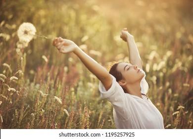 Free Happy Woman Enjoying Nature. Beauty Girl Outdoor. Freedom concept. Beauty Girl against sunny flowers field. Sunbeams. Enjoyment.