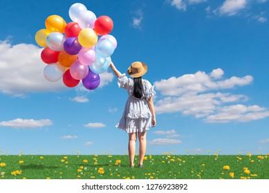 free happy woman enjoying sunrise. Beautiful woman with holding balloon in blue sky enjoying peace