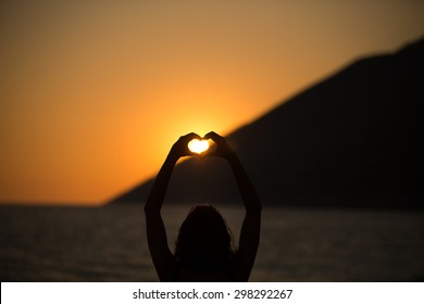 Free happy woman enjoying sunset..Embracing the golden sunshine glow of sunset,enjoying peace,serenity in nature.Vacation vitality healthy living concept.Silhouette hand in heart shape
