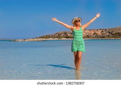 Free happy woman in green striped dress enjoying relaxing beach, joyful in summer by tropical blue water on Elafonisi beach, Greece.