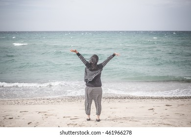 free happy woman open arms  in front of the sea, on a windy day