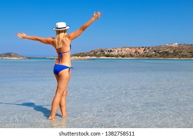 Free happy woman raising arms and enjoying beach relaxing joyful in summer by tropical blue water. Beautiful bikini sexy model happy on travel wearing beach sun hat on Elafonisi beach, Greece.