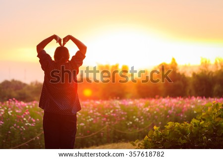 Free happy woman raising arms with love watching the sun in the background