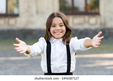 Free hugs. Come here. Schoolgirl pull hands to you. Smiling schoolgirl sincere child glad to see you. Welcome back to school. Come and give me hug. Happy schoolgirl wide open hug. Nice to meet.