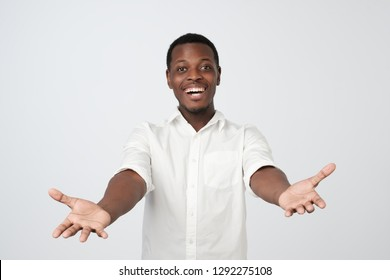 Free hugs for person who had bad day. Cheerfull african man in white shirt, pulling hands towards camera, wanting to cuddle, smiling broadly, welcoming friends or guests.