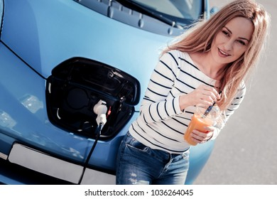 Free minute. Calm pretty pleasant woman drinking juice near her car looking aside and waiting when the car will be charge.