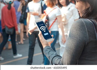 free public Wifi concept.Young woman holding mobile phone on blurred people walking as background