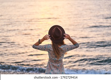 Free serene boho woman wearing dress and felt hat standing back by the seashore at sunset and enjoying calm and freedom