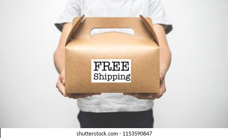 Free Shipping concept - Hand of a boy holding a box written FREE SHIPPING.
