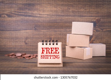 Free shipping concept. Paper boxes on wooden background. Selling goods or services online over the internet