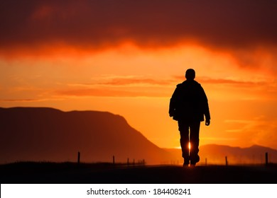 free silhouette man walking on the road among the mountains, clouds, backlit at sunset