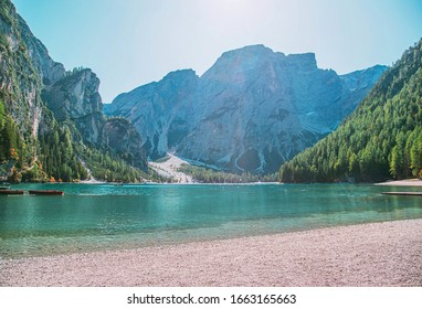 Free space for inscription text poster backdrop of Italian lake of Braies boats float on emerald water Alps in sun light green forest on side mountains tourists relax fantastic nature. Photo wallpaper