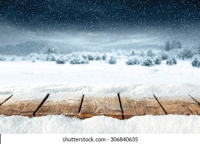 free space on wooden desk top and snow with frost and sky of blue color