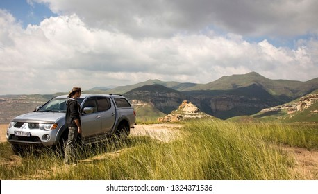 Free State, South Africa - March 22, 2016: Young man standing next to his off-road Mitsubishi car looking at Drakensberg mountains. Golden Gate Highlands National Park. Amazing African landscape.