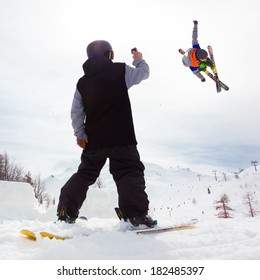 Free style skier performing a high jump. Buddy filming it on a Gopro camera. Ski lifts in the mountains in the background.