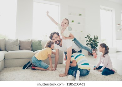 Free time, careless, carefree leisure pre-teen concept. Father spend free time with kids play near sofa in modern white light interior, ride little girl on back