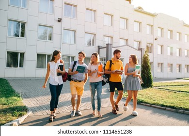 Free time of a students, bachelor`s campus life rhythm. Five friendly students are walking after they passed test outside the college building and discuss the project, smiling, enjoying, carefree