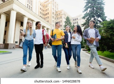 Free time of students. Friends walking after classes against university building