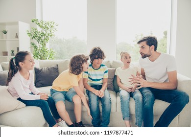 Free time talk concept. Babysitter tell scare story actively gesticulating with his hands and sit on couch in modern white light interior, children hold palms near face, make big eyes and open mouth