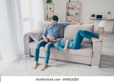 Free time together. Happy beautiful couple is spending weekend together on couch indoors at home, relaxing and enjoying the company of each other