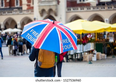 Free tour on a Cracow market square, a UK english guide with a united kingdom flag umbrella seen from the back. Local free of charge tourist guides. Tourism, travelling for england residents concept