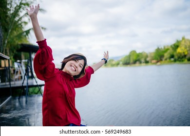 Free woman enjoying freedom feeling happy at lake. Beautiful serene relaxing woman in pure happiness and elated enjoyment with arms raised outstretched up. Asian Caucasian female model.