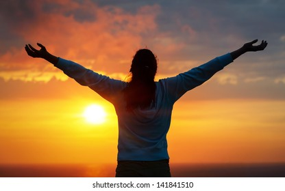 Free woman raising arms to golden sunset summer sky and ocean like praising. Freedom, success and hope concept. Girl relaxing and enjoying peace and serenity on beautiful nature.