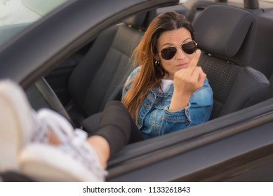 Free woman showing middle finger enjoying her convertible car. Freedom woman concept.