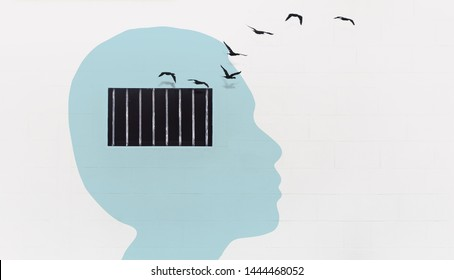 Free your mind concept and think out of the box concept, light blue human head with security window bar on the white wall with birds flying out from the window