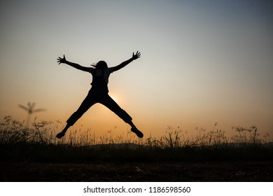 Freebom concep, a young woman jumping in the middle of a meadow in the light of the falling sun. In the evening