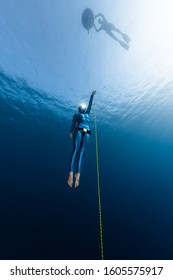 Freediver ascends along the rope from the depth while another freediver relaxes on the buoy