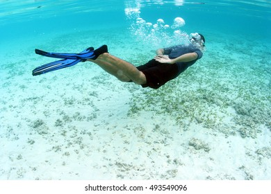 Freediver Asian man in blue rashguard and black shorts with blue fins swim close to white sand and seaweed in clear blue sea, Indo-pacific ocean, Southeast Asia