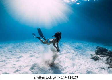 Freediver girl with fins dive over sandy sea in ocean.