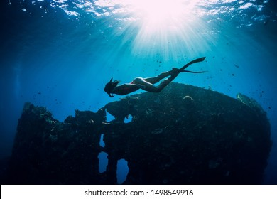 Freediver girl in pink swimwear with fins swimming underwater at wreck ship. Freediving in blue ocean