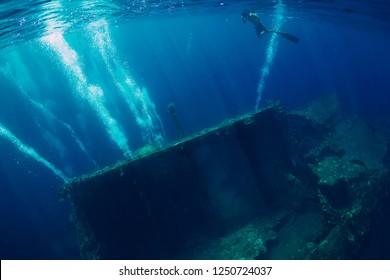 Freediver man swim in sea near shipwreck in Bali