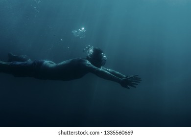 Freediver sporty young man swimming underwater, breaststroke.