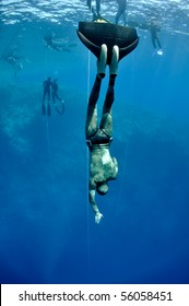Freediver starts his descent from the surface to the depth. There are other freediver teams at the background.