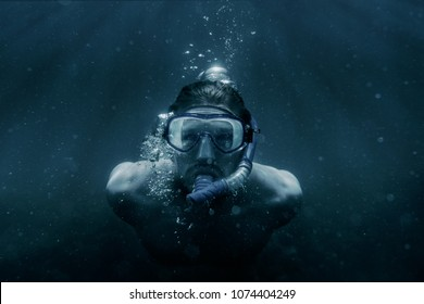 Freediver young man in mask and snorkel swimming underwater among sunbeams, front view.