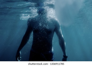 Freediver young man swimming to the surface of sea to breathe.